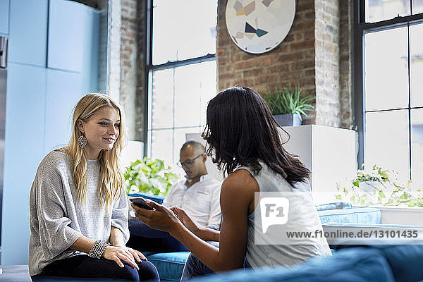 Businesswoman discussing over smart phone while male colleague sitting at creative office