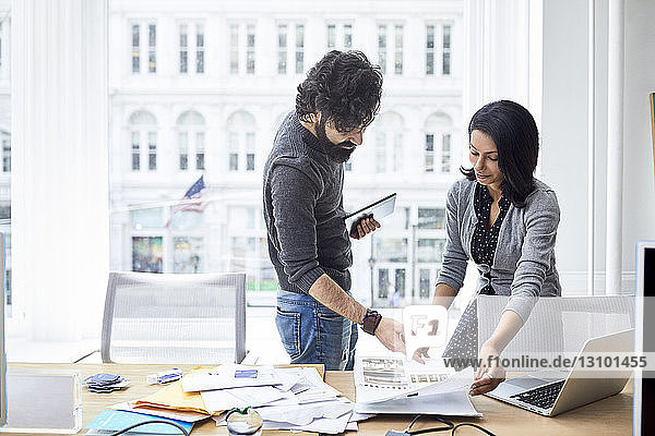 Businesswoman showing documents to male colleague while standing against window in creative office