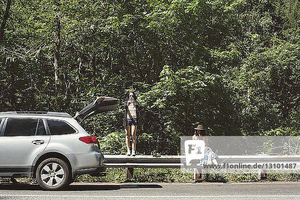 Freundinnen auf einem Geländer im Auto gegen Bäume bei Sonnenschein