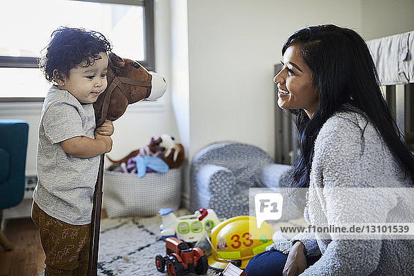 Cute son embracing hobby horse while playing with mother at home
