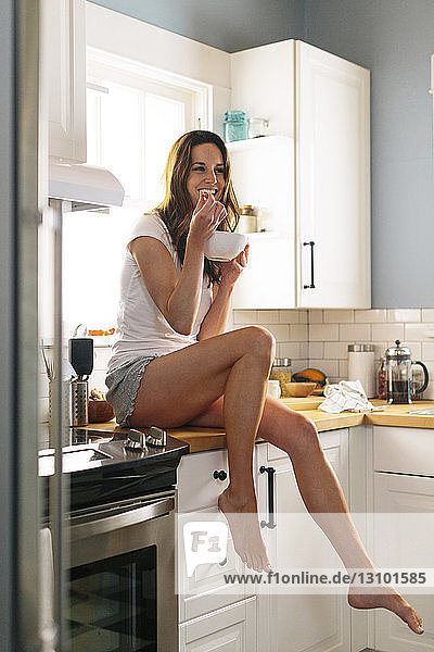 Happy woman having breakfast while sitting on kitchen counter at home
