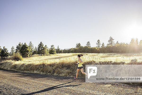 Frau in voller Länge auf dem Feld joggend vor klarem Himmel am sonnigen Tag