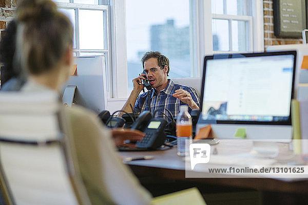 Geschäftsleute  die an Schreibtischen im Büro arbeiten