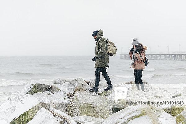 Paar mit Rucksäcken auf Felsen am Strand am Meer bei klarem Himmel