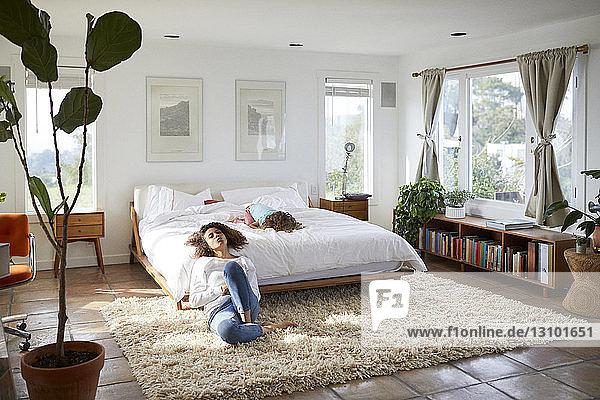 Mutter mit Tochter entspannt sich zu Hause im Schlafzimmer