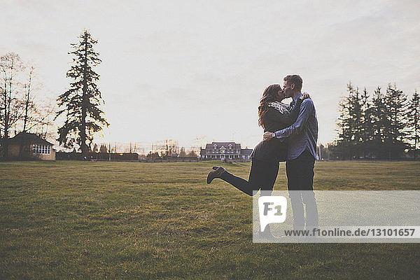 Romantisches Paar küsst sich im Stehen auf Grasfeld gegen den Himmel