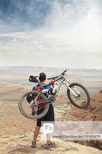 Rear view of man lifting bicycle while standing on cliff against sky