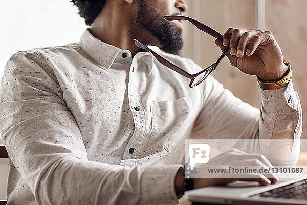 Mittelteil eines Mannes  der eine Brille hält  während er einen Laptop am Tisch benutzt