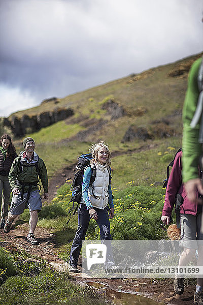 Happy female hiker with friends walking on hill