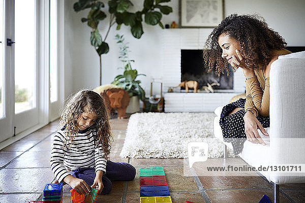 Mother looking at daughter playing with toy blocks in living room