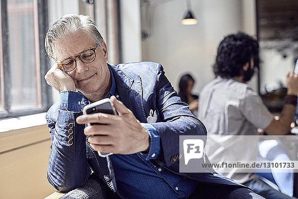 Geschäftsmann betrachtet Smartphone mit einem männlichen Kollegen im Hintergrund