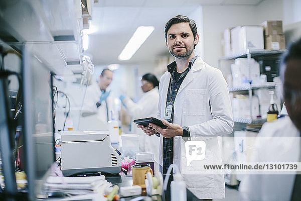 Porträt eines männlichen Arztes mit Tablet-Computer und Mitarbeitern  die im Krankenzimmer arbeiten