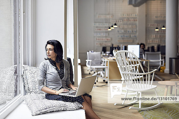 Businesswoman looking through window while using laptop computer with male colleagues sitting in background