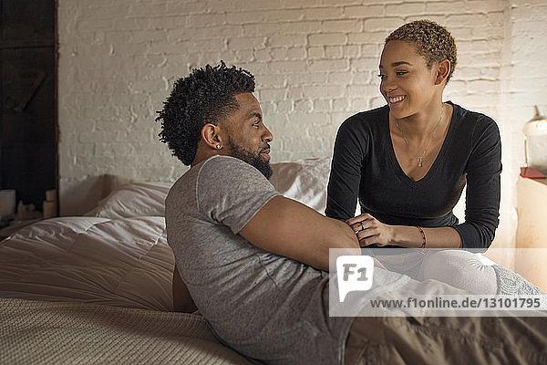 Glückliches junges Paar sieht sich im Schlafzimmer an
