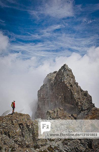 Hochwinkelaufnahme eines Wanderers  der auf einem Berg inmitten von Wolken steht
