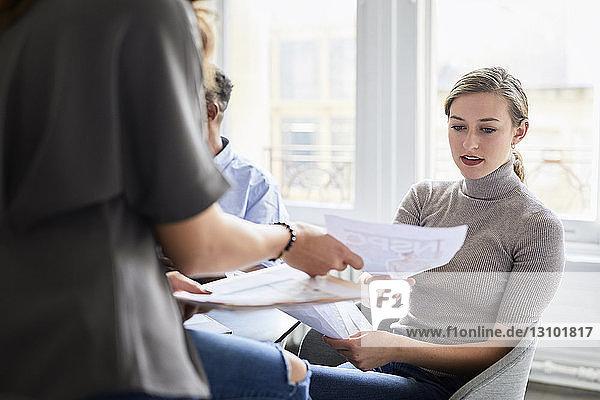 Weibliche Kollegen diskutieren Dokumente im Kreativbüro