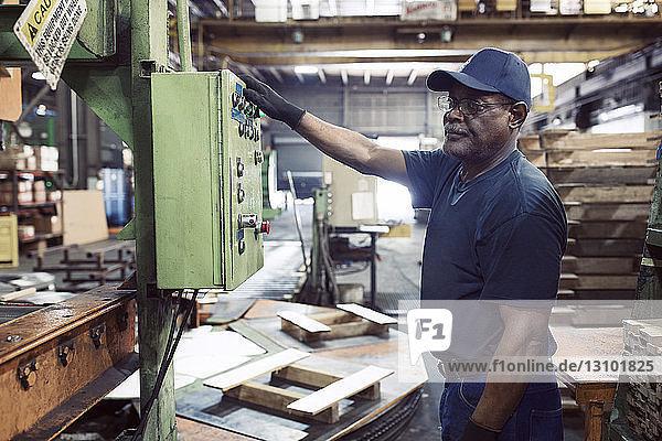 Seitenansicht eines Arbeiters  der eine Maschine bei der Arbeit in der Stahlindustrie benutzt