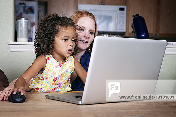 Mother and daughter using laptop at table