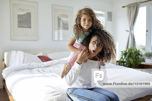 Portrait of daughter playing with mother sitting on bed at home