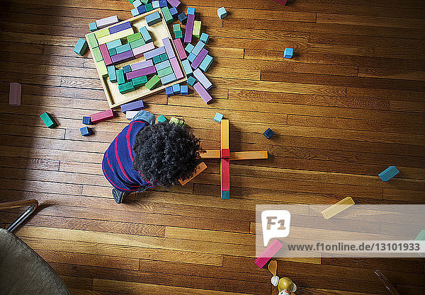 Overhead view of boy playing with toy blocks on hardwood floor at home