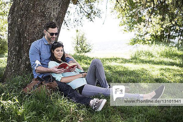Paar liest Buch beim Entspannen am Baum im Park