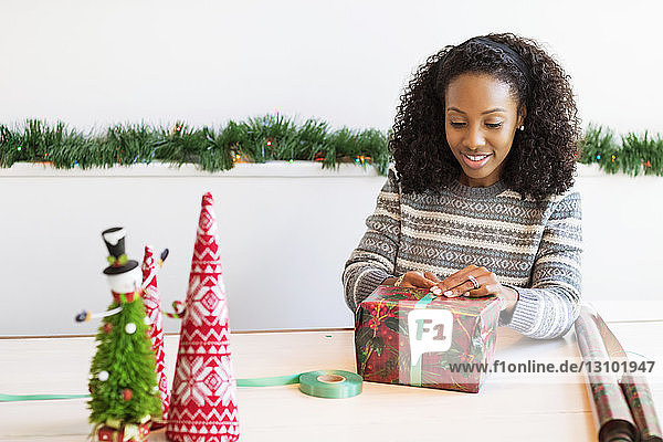 Frau packt Weihnachtsgeschenk ein  während sie am Tisch sitzt