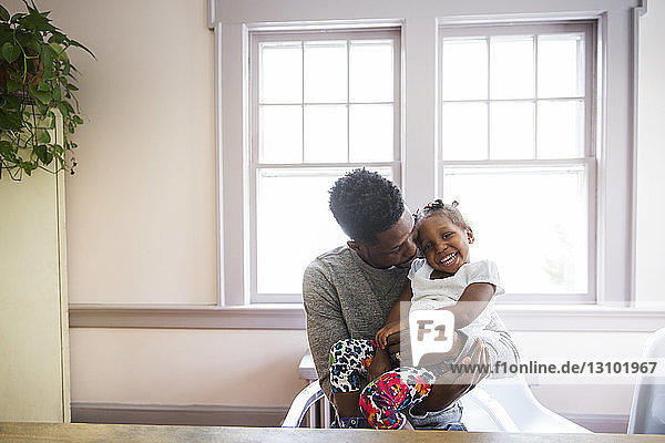 Portrait of happy girl sitting with loving father at home