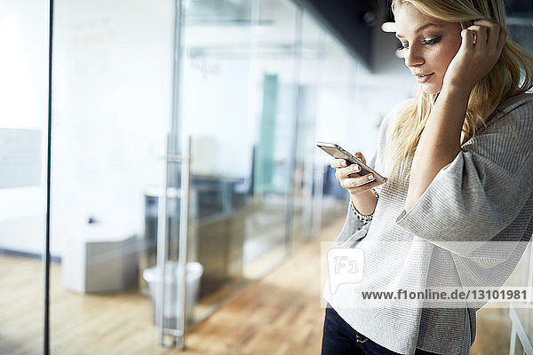 Young businesswoman using mobile phone while standing at corridor