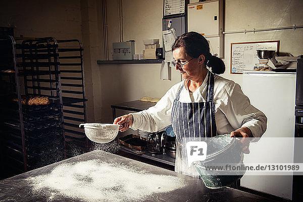 Female baker sprinkling flour on table at bakery