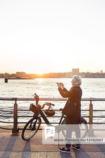 Full length of senior woman photographing while standing on promenade during sunset