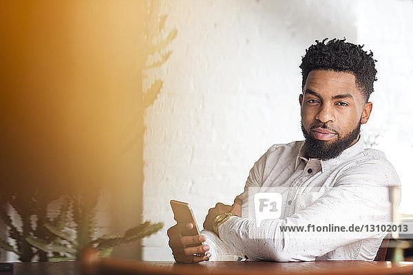 Porträt eines selbstbewussten Mannes mit Smartphone am Tisch sitzend