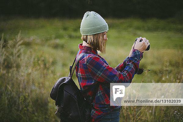 Seitenansicht einer Frau  die im Stehen auf einem Grasfeld fotografiert