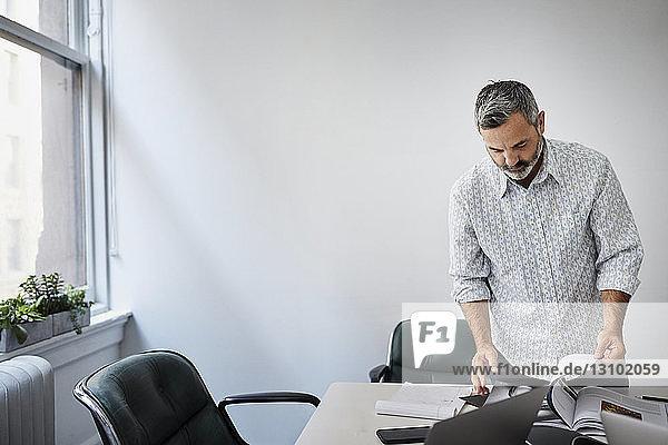 Geschäftsmann betrachtet Buch  während er am Konferenztisch an der Wand im Sitzungssaal steht