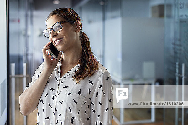 Smiling businesswoman talking on mobile phone while standing in corridor