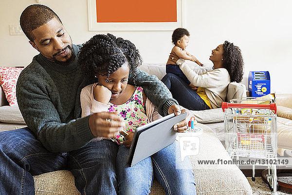 Vater und Tochter benutzen einen Tablet-Computer  während die Mutter mit dem Sohn auf dem Sofa spielt