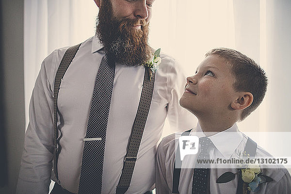 Smiling bridegroom and pageboy looking at each other while standing against curtain