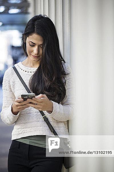 Junge Frau benutzt Smartphone  während sie sich an die Wand lehnt
