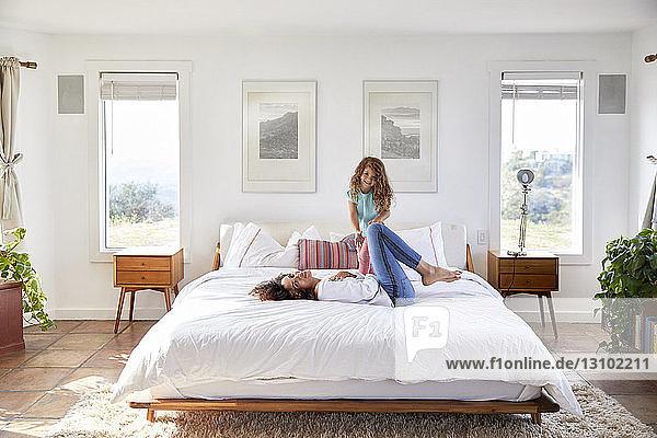 Porträt von Mutter und Tochter beim Spielen im Bett zu Hause