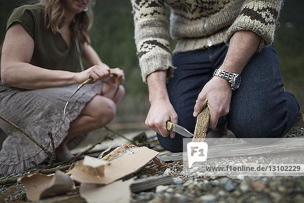 Freund schneidet in der Mitte Holz,  während seine Freundin auf dem Campingplatz kniet