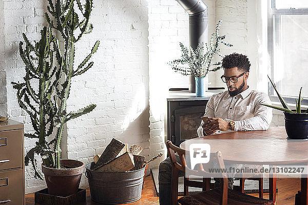 Junger Mann benutzt zu Hause ein Smartphone