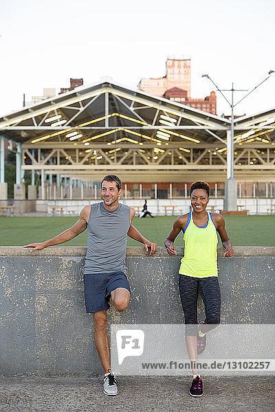 Porträt einer Sportlerin mit Freundin an der Stützmauer stehend, Porträt einer Sportlerin mit Freundin an der Stützmauer stehend