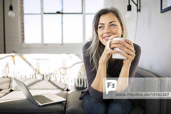 Smiling woman holding coffee mug while sitting by laptop on sofa in living room