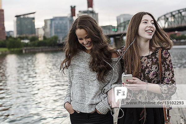 Lächeln in Freunden  die Musik hören  während sie gegen die Burlington Northern Railroad Bridge stehen 9 6