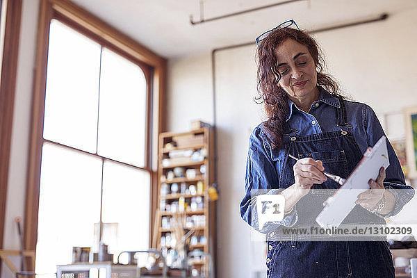 Niedrigwinkelansicht einer Künstlerin  die in einer Werkstatt arbeitet