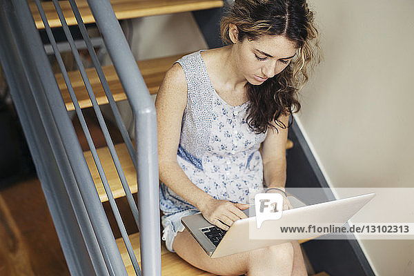 High angle view of woman using laptop on staircase