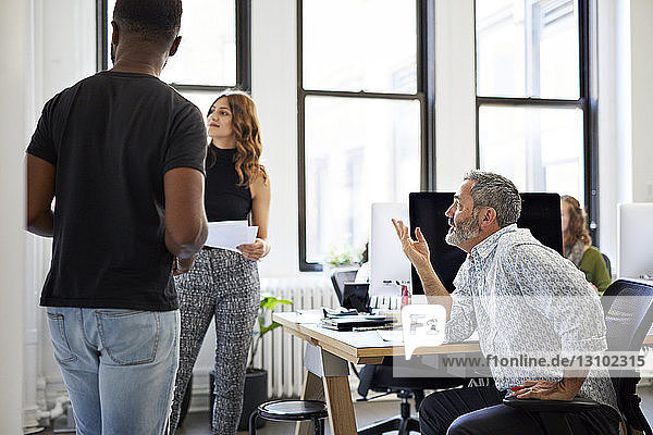 Geschäftsmann gestikuliert bei der Arbeit mit Kollegen im Sitzungssaal