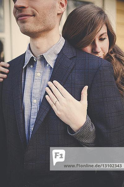 Mittelteil des Ehemannes wird von der Ehefrau umarmt