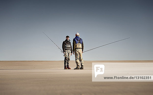 Friends holding fishing rods while standing on sand against clear sky