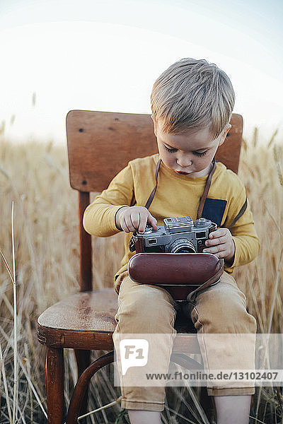 Curious boy adjusting vintage camera while sitting on chair amidst wheat field