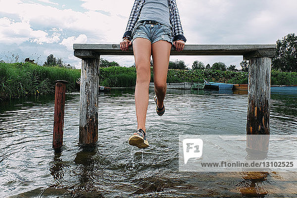 Low section of teenage girl playing with water while sitting on bench over lake